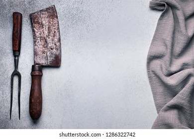 Meat cleaver and fork on concrete with copy space. Food background