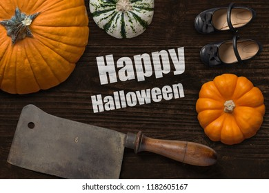 """meat cleaver, pumpkins and girl shoes on wooden background and the message """"Happy Halloween"""""""