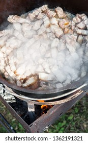 Meat is cooking in the pot, meat on the fire for rice pilau outdoors. Camping in the nature and preparing food concept