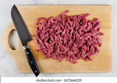 Meat for cooking stir fry on cutting board. Step-by-step cooking
