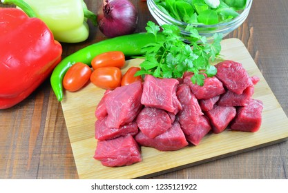 Meat cubes, raw pork,beef,veal on kitchen board with vegetables and ingredients for cooking goulash or stew