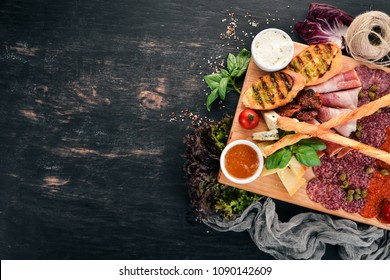 Meat cut and cold snacks. Italian cuisine. On a wooden background. Top view. Copy space.