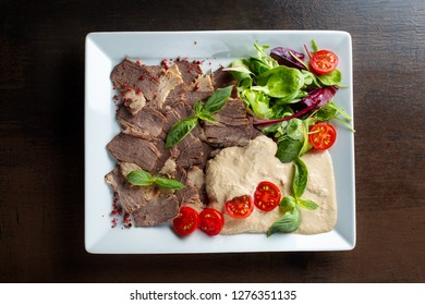 Meat cut with horseradish on a white plate. Top view. Diagonal composition.