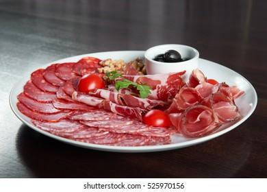 Meat deli. Assorted salami and ham plate decorated with cherry tomatoes black olives and walnuts
