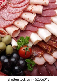 meat delicatessen plate arranged with cherry tomato, black and green olives and parsley