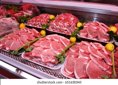 Meat department shelves with typical Italian raw meat inside a market. Pork chops, display in the meat department.