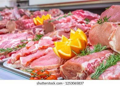 Meat department, showcase with variety of meat in different cuts. Inside an Italian supermarket. Different types of fresh meat arranged in an orderly manner.