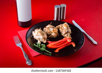 Meat dish with paprika, salad and a bottle of wine on a red background. Dinner at the restaurant