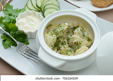 Meat dumplings with dill and sauce garnished with sour cream and cucumber slices