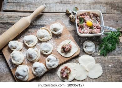Meat dumplings - russian pelmeni on wooden background