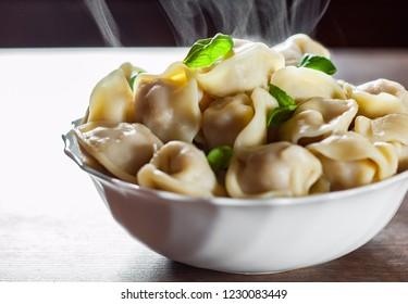 Meat dumplings - russian pelmeni, ravioli with meat in bowl on a wooden table background
