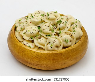 Meat dumplings - russian pelmeni, ravioli with meat on a wooden plate on a white background, isolated