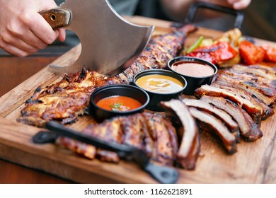 Meat Food. Barbecue Ribs And Sauces In Restaurant On Wooden Tray. Man's Hands With Ax Cutting Pork Ribs. High Resolution