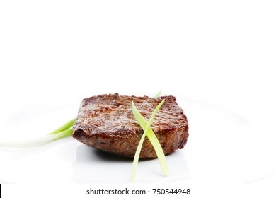meat food : roast beef fillet mignon served on white plate with green sprouts isolated over white background