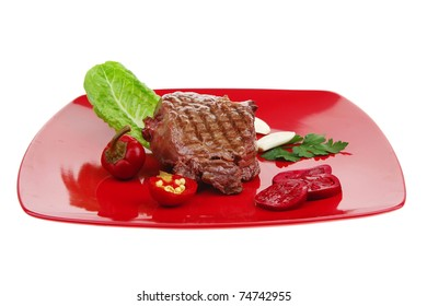 meat food : roast beef garnished with green lettuce and red chili hot pepper on red plate isolated over white background