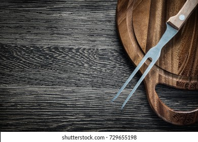 Meat fork wooden chopping board on wood background.