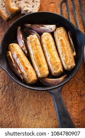 Meat free (quorn) mycoprotein sausages with red onions on skillet