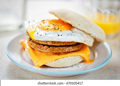 Meat free sausage flavour patties with cheese and egg on breakfast muffin