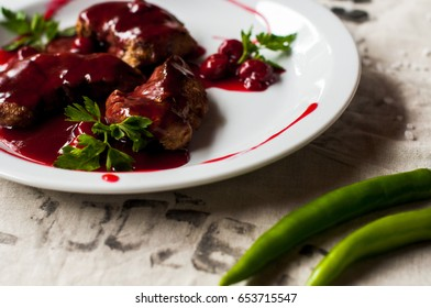 meat with fresh herbs and cherry sauce, ready to eat.