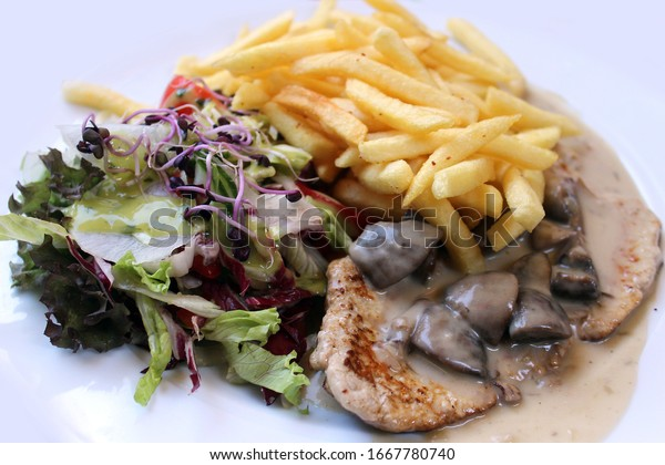 meat with fries and a green salad