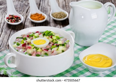meat, greens and vegetables cold summer soup with  serum and yogurt sprinkled with parsley and sprting onion in white cup with spices and mustard in gravy boat  view from above, close-up
