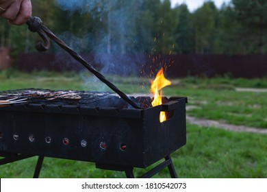 The meat is grilled. A man stirring coals with a hot poker. Sparks fly from the fire in the grill. Outdoor cooking. Meeting with friends, picnic, weekend. Evening outdoor recreation.