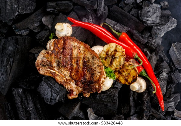 meat grilling on coal background with mushrooms, garlic and red pepper