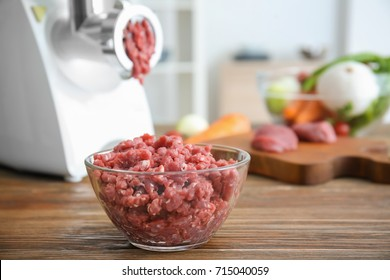 Meat grinder with fresh forcemeat on kitchen table