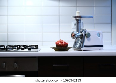 Meat grinder with fresh meat on kitchen table