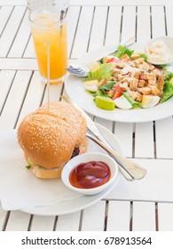 Meat hamburger with vegetable salad and orange juice as meal set serve at restaurant