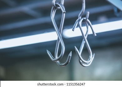 Meat hooks hanging in a slaughterhouse.
