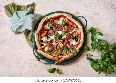 Meat Italian pizza with roast beef, chicken slices, melted cheese, red tomatoes and green basil sauce on a tray decorated by basil leaves and black olives. Pizza time concept. Copy space, top view