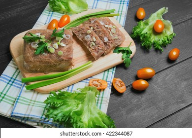 Meat jelly aspic galantine, yellow cherry tomatoes, parsley, lettuce, wooden cutting board, on a dark black background surface