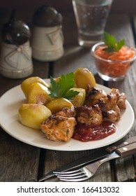 Meat kebab with baked potato and tomato sauce, selective focus