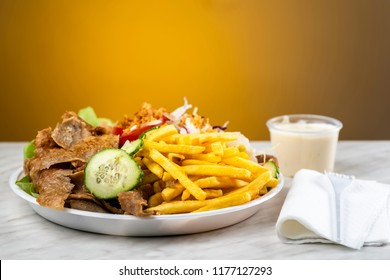 meat with kebab, French fries and salad on a plastic plate