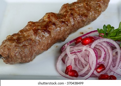 Meat kebab served onion, parsley and pomegranet seeds