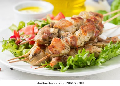 Meat kebabs (chicken, Turkey, pork) on wooden skewers with vegetable salad and yogurt sauce. Spring picnic, grilled food, delicious lunch. On light background