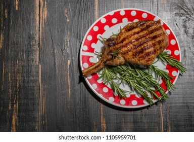 meat lies in a plate on top of a rosemary. dark wooden background with cooked pork rib and spices