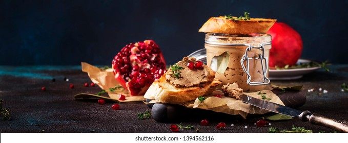 Meat liver pate on toasted bread with fruit seeds and spice herb, brown kitchen table, copy space, selective focus