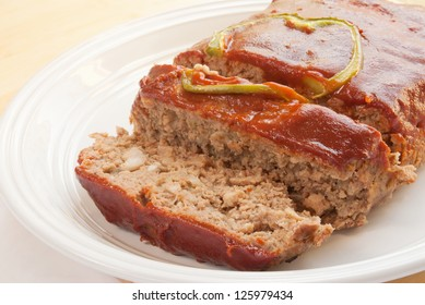 meat loaf made from lean ground beef. There is a green bell pepper slice on the top. The sauce is ketchup based.