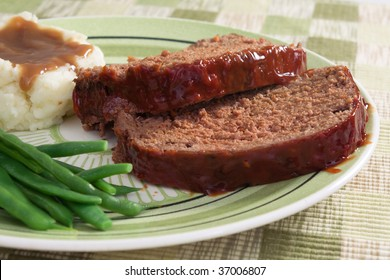 Meat loaf prepared with ground beef, grated carrots, bread crumbs, and herbs and spices. Served with fresh green beans, mashed potatoes, and gravy.