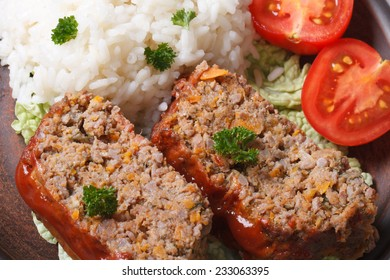 meat loaf with rice and vegetables on a plate macro horizontal view from above