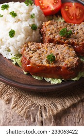 meat loaf with rice and vegetables on a plate close-up, vertical