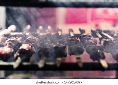 Meat on the grill. Grilled meat and spit-roasted meat during cooking