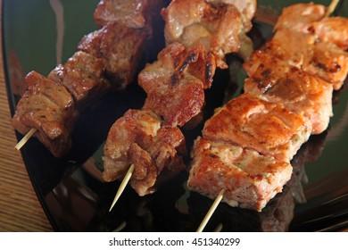meat on skewer on a black plate