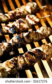 Meat on skewers being flame grilled on a BBQ.