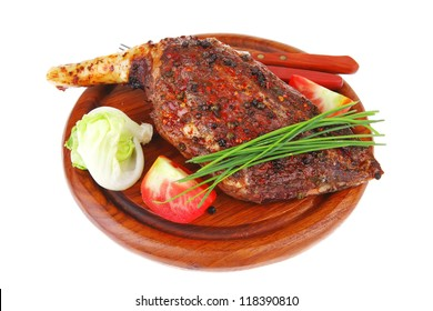 meat on wooden plate : roast shoulder on wood with tomatoes chives and green lettuce isolated on white background