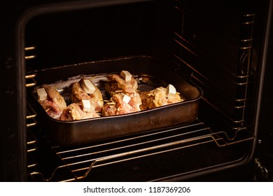 Meat in the oven for baking for dinner. The process of cooking a recipe
