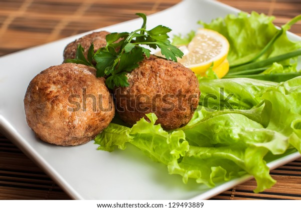 Meat patties in the plate with lettuce and parsley