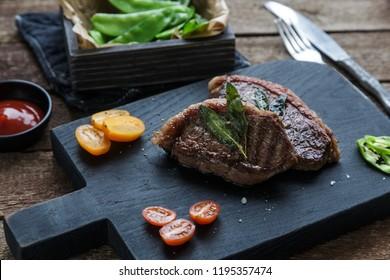 Meat Picanha steak, traditional Brazilian cut on black cutting board.